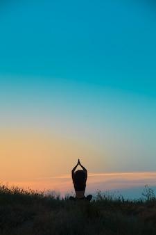 La silueta de una mujer joven practica yoga