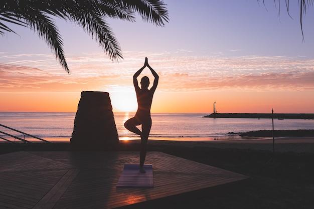 Silueta de mujer joven practicando yoga al amanecer frente a la playa