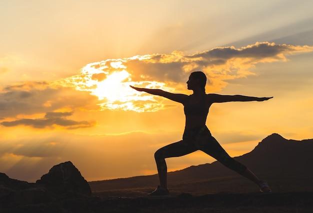 Silueta de mujer joven practicando yoga o pilates al atardecer o amanecer en la hermosa ubicación de montaña.
