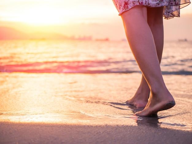 Silueta de la mujer joven que camina solamente en la playa en la puesta del sol.