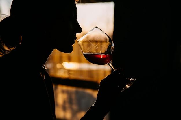 Silueta de una mujer joven sosteniendo una copa de vino tinto en la luz del atardecer