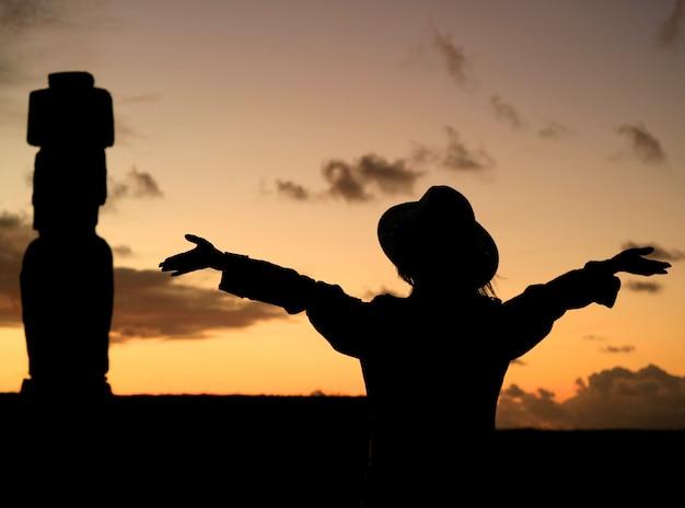 Silueta de mujer levantando los brazos admirando el cielo del atardecer con la estatua de moai en la isla de pascua, chile