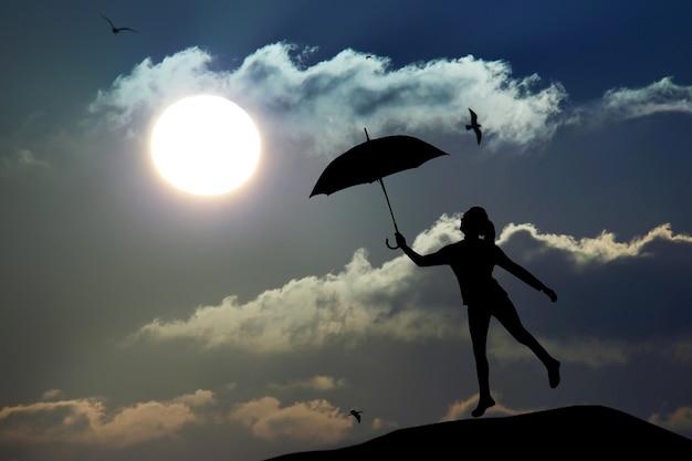 Silueta de mujer paraguas saltar y atardecer con gran sol, paisaje