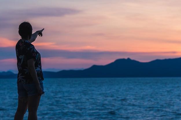 Silueta de una mujer de pie con la puesta de sol en el hermoso mar