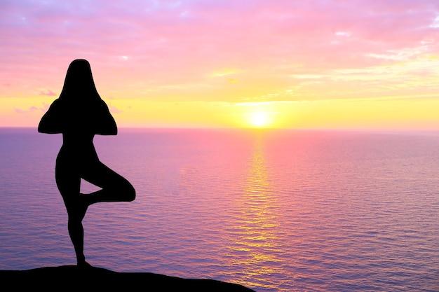 Silueta de mujer practicando yoga durante la puesta de sol en la playa.