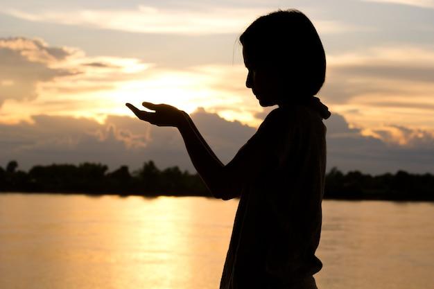 Silueta de mujer rezando sobre fondo hermoso atardecer.