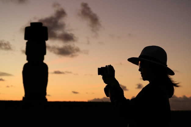 Silueta de mujer turista tomando fotos de la estatua de moai en ahu tahai, isla de pascua, chile