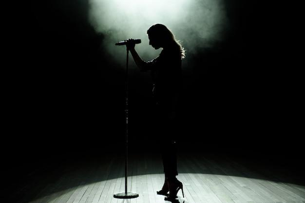 Silueta negra de cantante femenina con focos blancos en el fondo