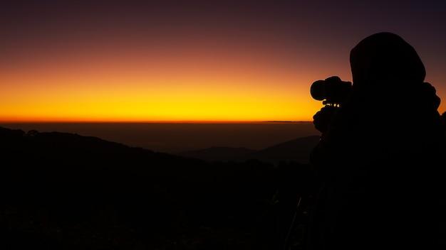 La silueta negra del fotógrafo tomando fotos