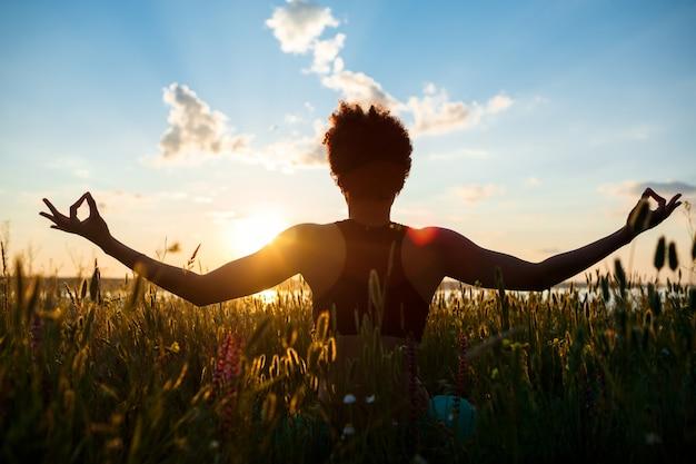 Silueta de niña deportiva practicando yoga en el campo al amanecer.