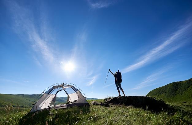 Silueta de niña excursionista con mochila de pie en la cima de una colina contra el cielo azul, el sol y las nubes cerca de la tienda, levantando las manos en el aire con bastones de trekking en las manos, disfrutando el día de verano