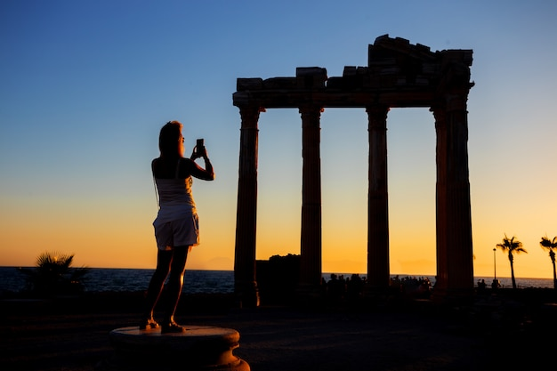 Silueta de niña fotografiando por teléfono el templo de apolo al atardecer