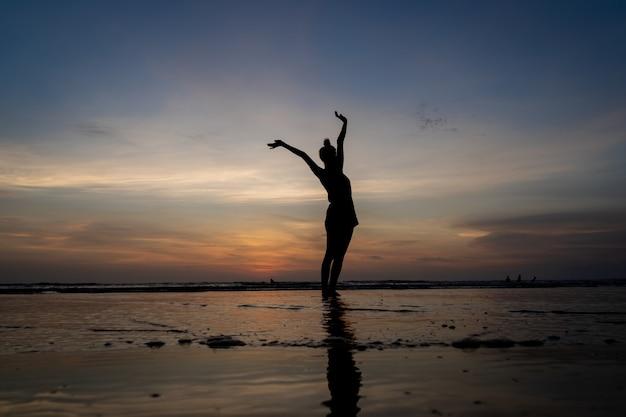Silueta de una niña de pie en el agua con los brazos levantados gesticulando