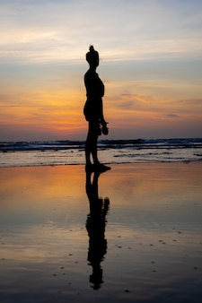 Silueta de una niña de pie en el agua en una playa