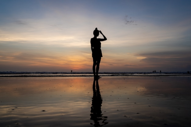 Silueta de una niña de pie en el agua tocando su cabello en una playa