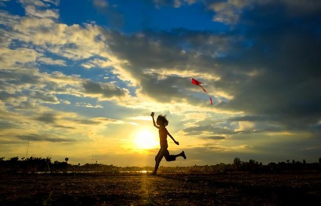 Silueta de la niña volando una cometa en la puesta del sol.