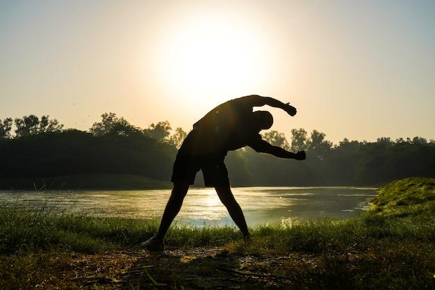 Silueta de un niño haciendo ejercicios en el parque cerca del sol y el río - concepto de salud