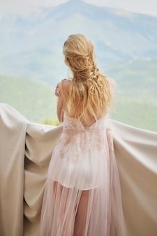 Silueta de la novia hermosa de la muchacha en los soportes de un peignoir del balcón que pasa por alto las montañas
