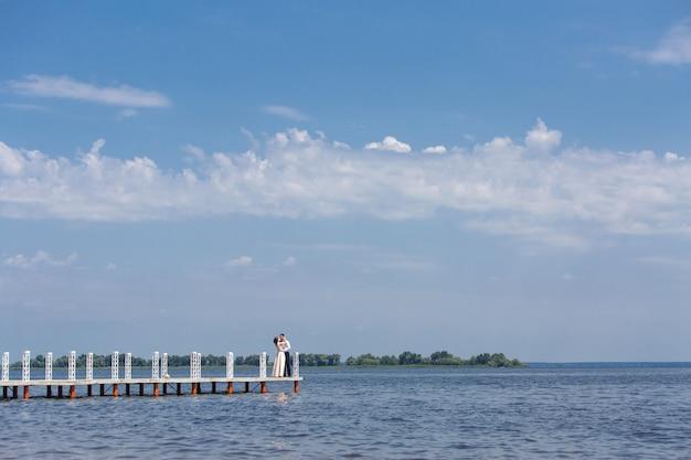 Silueta de novios caminando por el puente en un día soleado. día de la boda. hombre y mujer abrazando y besando al aire libre. retrato de feliz pareja enamorada de la naturaleza