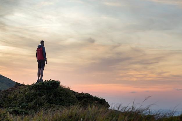 Silueta oscura de un excursionista en una montaña al atardecer de pie en la cumbre como un ganador.