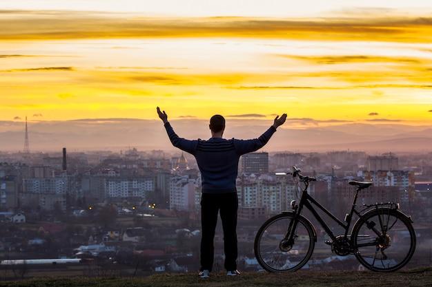 Silueta oscura de un hombre parado cerca de una bicicleta con la vista nocturna de la ciudad