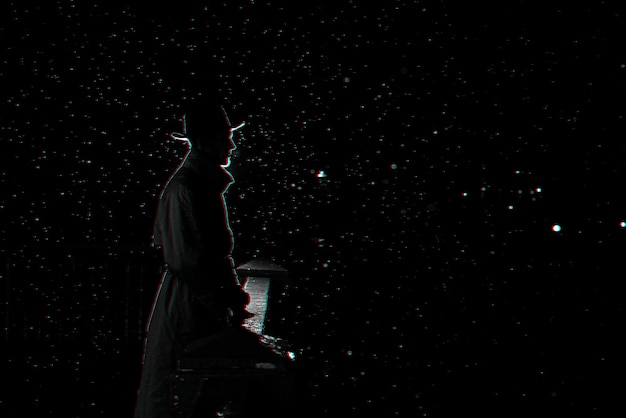 Silueta oscura de un hombre con sombrero por la noche bajo la lluvia en la ciudad. blanco y negro con efecto de realidad virtual 3d glitch