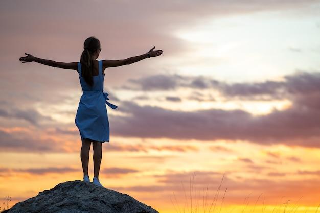 Silueta oscura de una mujer joven de pie con las manos levantadas sobre una piedra disfrutando de la vista del atardecer al aire libre en verano.