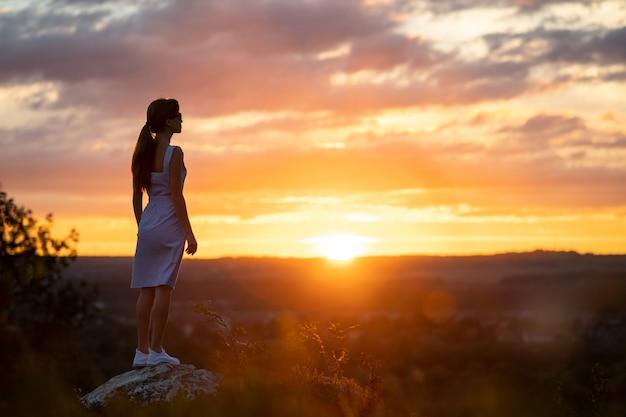 Silueta oscura de una mujer joven en vestido de verano de pie al aire libre disfrutando de la vista de la naturaleza