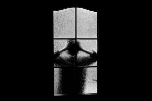 Silueta oscura de niña detrás del vidrio