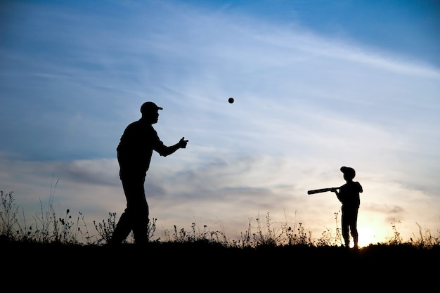 Silueta de padre e hijo jugando béisbol en concepto de deporte familiar de naturaleza