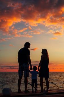 Silueta, de, padres, con, un, niño, en el mar
