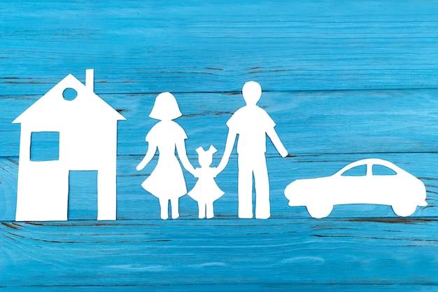 Silueta de papel de familia con casa y auto