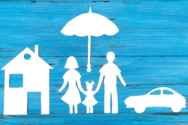 Silueta de papel de familia bajo paraguas