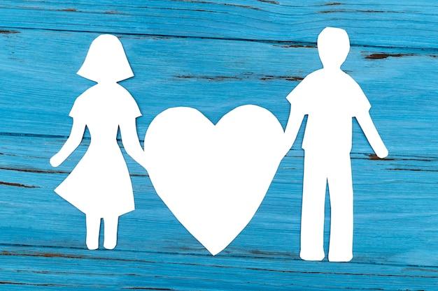Silueta de papel de hombre y mujer con corazón