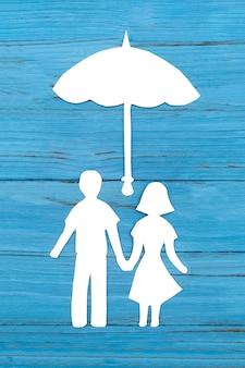 Silueta de papel de hombre y mujer tomados de la mano bajo paraguas