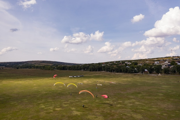 Silueta de parapentes volando sobre un hermoso paisaje verde bajo un cielo azul con nubes.