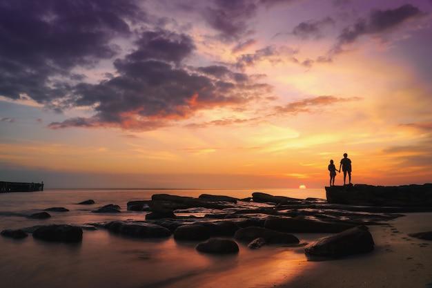 Silueta de pareja cogidos de la mano y mirando la puesta de sol en la playa del mar en tiempo hermoso.
