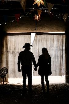 Silueta de una pareja cogidos de la mano en una tienda de campaña bajo las luces