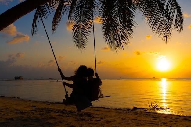 Silueta pareja de enamorados camina en la playa durante el atardecer. montar en un columpio atado a una palmera y ver la puesta de sol en el océano