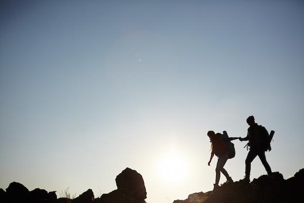 Silueta de pareja escalar montañas