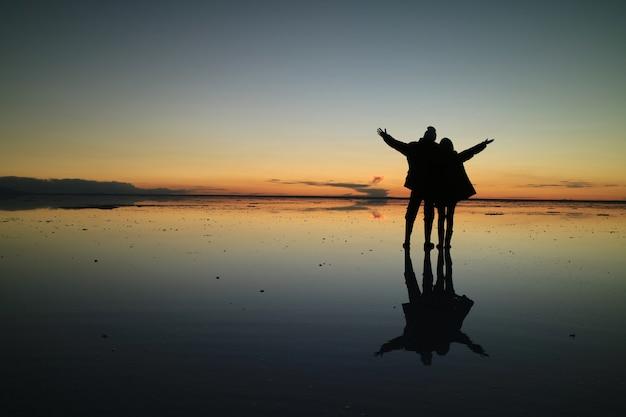 Silueta de una pareja en el increíble efecto espejo de uyuni salt flats, bolivia