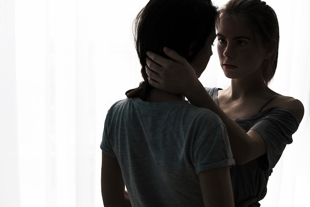Silueta de pareja de lesbianas jóvenes románticas mirando el uno al otro de pie contra la cortina blanca