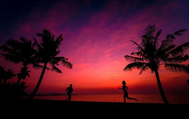 Silueta de pareja en playa tropical durante el atardecer en el fondo