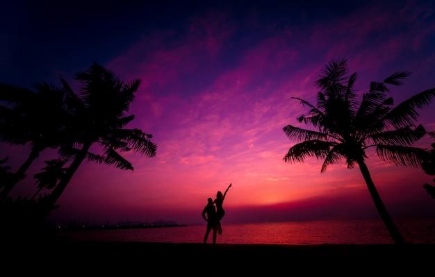 Silueta de pareja en playa tropical durante el atardecer