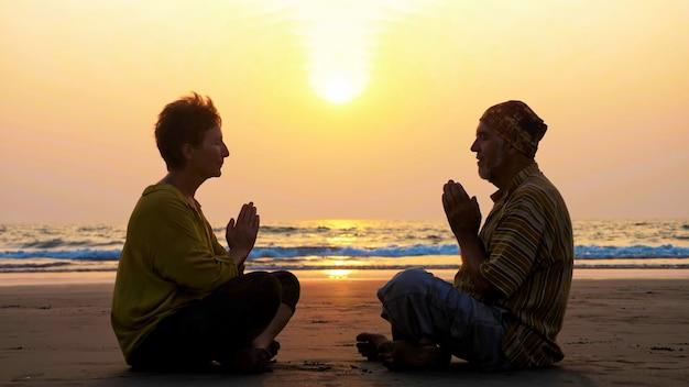 Silueta de pareja senior sentada y meditando juntos en la playa de arena