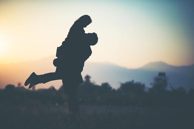 Silueta de pareja en la silueta de amor durante la puesta de sol