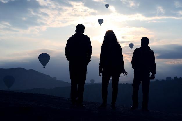 Silueta de personas mirando el vuelo matutino de globos de pasajeros en capadocia