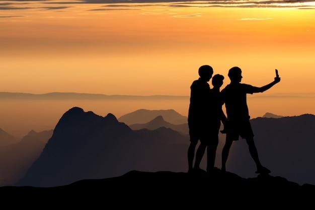 Silueta de personas que toman selfie en el acantilado en las montañas con puesta de sol en la noche