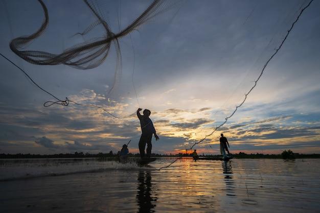 Silueta de pescador en barco de pesca con red en el lago al atardecer, tailandia