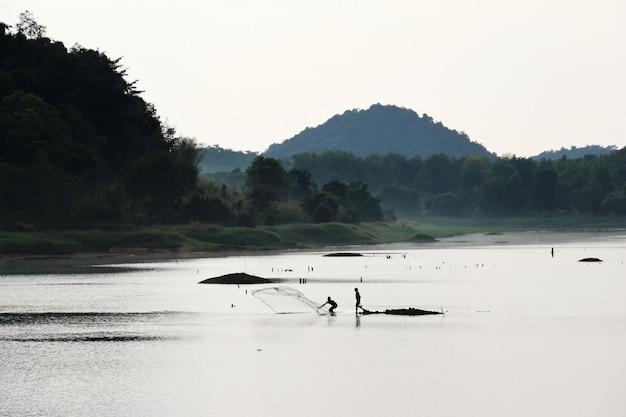 Silueta de pescador lanzando red de pesca en el embalse